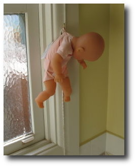 Baby drying on hook. Not real baby. Doll baby.